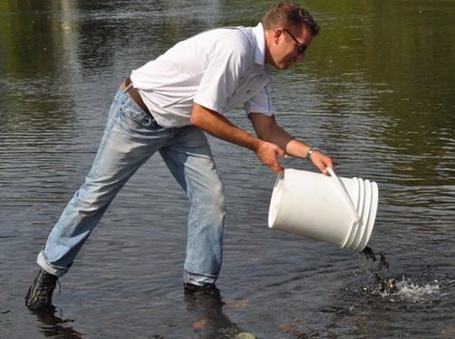 Glen Watson, Superintendent, Reclamation & Decommissioning for Vale's Ontario Operations, releases Rainbow Trout into the Onaping River in Dowling. The fish were raised at Vale's greenhouse in Copper Cliff.
