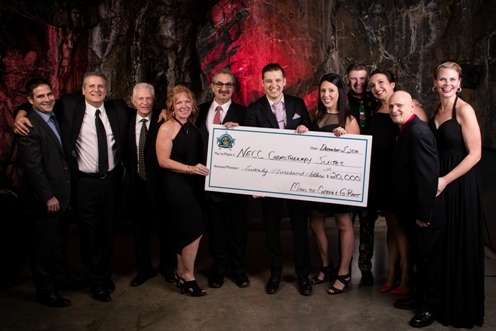 Members of Miners for Cancer alongside G-Rant from Newcap Radio's Hot 93.5FM seen here holding a $20,000 cheque that will go towards renovating the chemotherapy suites at the Northeast Cancer Centre in Sudbury, Ontario.